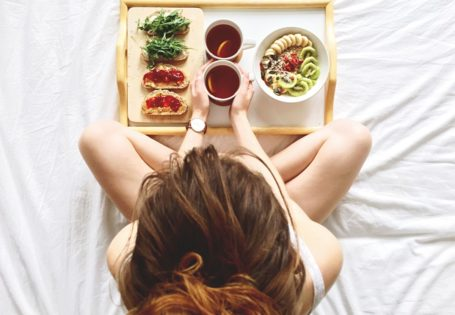 Mujer comiendo sobre cama
