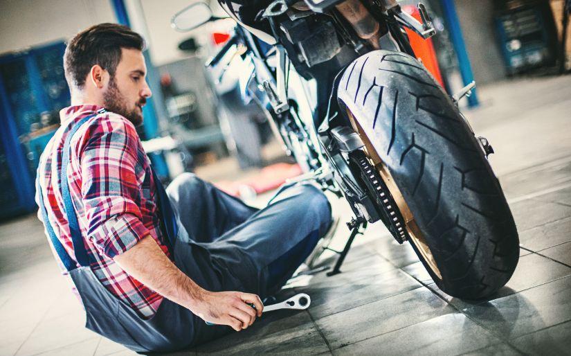hombre arreglando moto