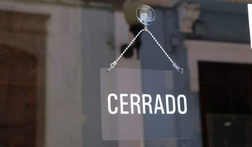 Puerta de comercio con cartel de cerrado